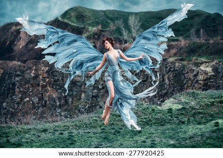 Stock Photo  Girl angel with a beautiful wings. As the picture from an old book. She takes off into the sky. Mountains in the background. Early spring. Fashionable toning, picture in the style of fantasy.