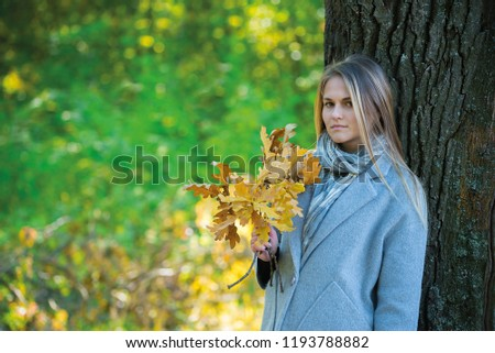 girl covers her face with oak branches. Woman covers her face with dry yellow oak leaf in autumn forest. autumn portrait in the park. girl in a gray coat. a red umbrella stands by a big oak #1193788882