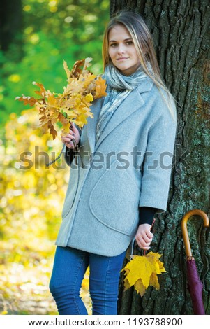 girl covers her face with oak branches. Woman covers her face with dry yellow oak leaf in autumn forest. autumn portrait in the park. girl in a gray coat. a red umbrella stands by a big oak #1193788900