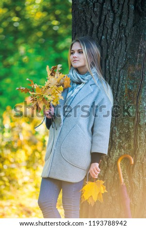 girl covers her face with oak branches. Woman covers her face with dry yellow oak leaf in autumn forest. autumn portrait in the park. girl in a gray coat. a red umbrella stands by a big oak #1193788942