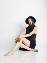А girl in a hat and dress sitting on a white background