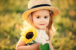 girl in a hat with a sunflower, summer portrait of a child, beautiful eyes