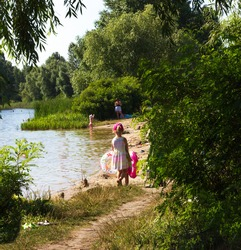 girl in a pink dress goes to the beach among the trees on the lake to swim girl holds two lifebuoys, sunny summer day