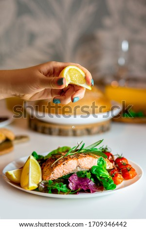 Girl pours fish with lemon juice.Only lemon with red fish.Grilled salmon steak.Salmon steak with lettuce, cherry tomatoes and lemon slices.Food for lunch.Fried red fish.Cooking salmon in the oven