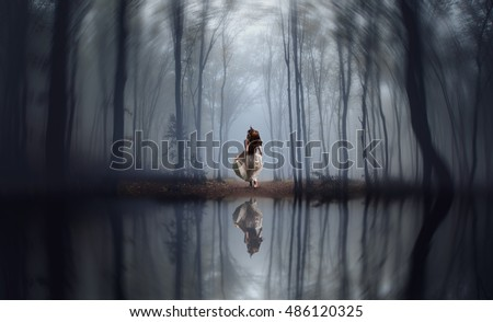 girl running in the middle of a foggy jungle on a winter day