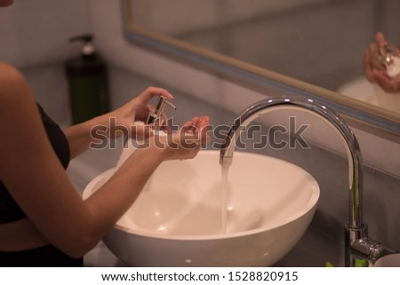 girl squeezes liquid soap from a bottle