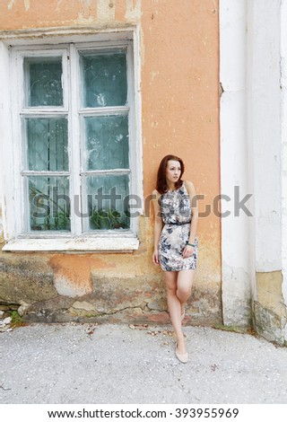 girl standing at the window of the old house