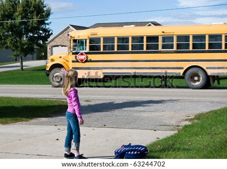 girl waving goodbye to school bus