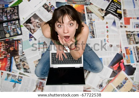 girl with a laptop sitting on newspapers