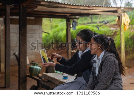 2 girls happy teenagers taking a selfie with a tablet.