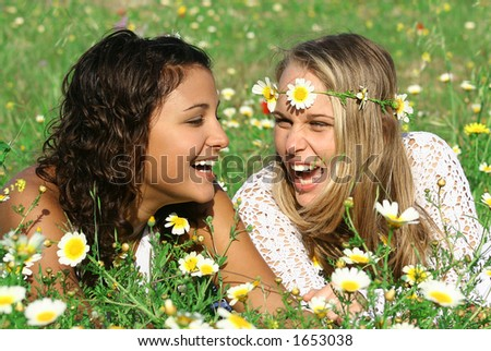 2 girls laughing in meadow of flowers.