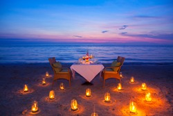 glass of wine And equipment on a wooden table with seascape and skyline in the evening with sunset tone style,Sunset is a romantic candlelight.