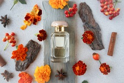 glass  perfume bottle with orange flowers, berries, cinnamon sticks and anise stars. Autumn wooden scent concept