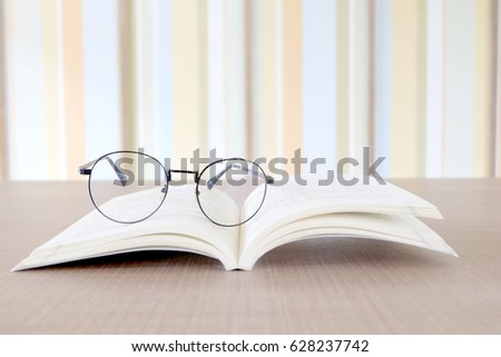 Glasses and books placed on table in the livingroom .Colorful background