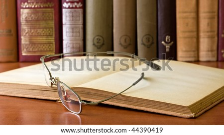 glasses in front of an old books in library