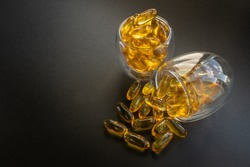 2 glasses of fish oil capsules with black background