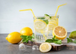2 glasses of lemonade with yellow lemon and mint, ice on a gray and   blue background, fresh citrus, refreshing drink