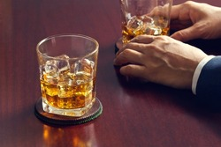 Glasses of whiskey in businessman's hands on wooden table background
