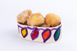 Glazed donuts placed on a box of typical Guatemalan sweets on white background