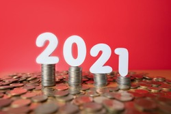 2021 Global economic crisis concept. Stack of coins with white number 2021 fall down on wood table over red background. Symbol for market fall, bankruptcy, business failure or finance crisis.