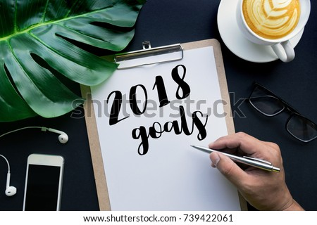 2018 goals concepts with hand writing on notepaper and business accessories laying on black table.flat lay/top view