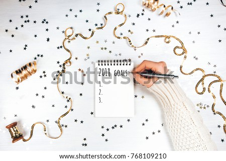 2018 goals. Festive decorations and notebook with wish list on white rustic table, flat lay style. Planning concept.