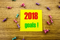 2018 goals on yellow sticky note, on wooden background. New Year resolutions concept. Goals 2018 concept.