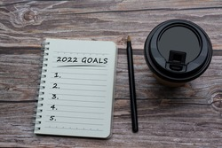 2022 goals text on notepad with a disposable coffee cup and pen on wooden desk