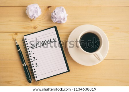 2019 goals text on notepad with coffee, pen and crumpled paper.                       #1134638819