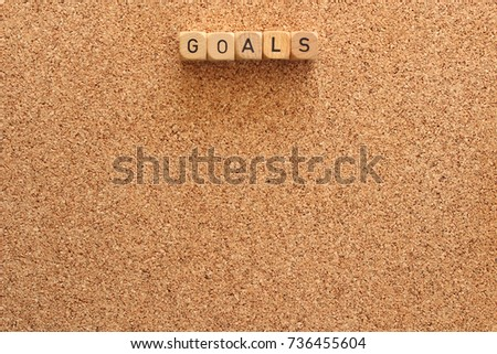 """Goals"" written on vintage wood blocks against cork board with copy space. #736455604"