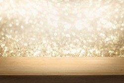 Gold color bright lights bokeh background of wooden table in front of lights abstract blurred and space use for product