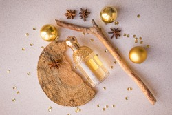 gold perfume bottle with wood fragments, golden balls, anise stars and sparkles