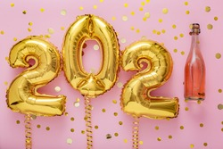 2021 golden air balloon numbers on pink background with bottle of rose champagne wine and confetti. Happy New year eve invitation card with Christmas gold foil balloons 2021. Flat lay long web banner