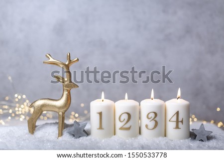 golden deko deer with burning advent candles against concrete background in the snow Stok fotoğraf ©