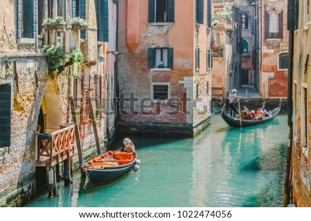 Gondolas on narrow canal and small boat tied next to old red brick house with wooden balcony on narrow canal in Venice, Italy. #1022474056