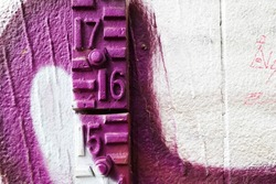 graffiti on the wall with concrete numbers sixteen purple and white
