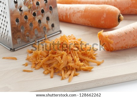 Grated orange carrots on a wooden board