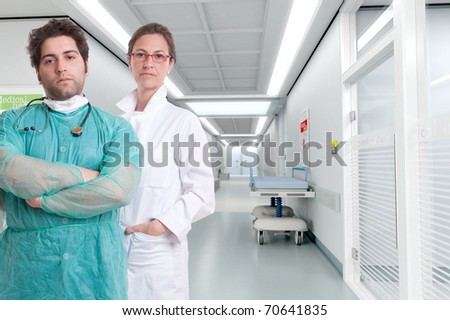 Grave looking hospital personnel standing by a corridor