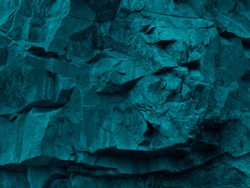 Green blue abstract grunge background. Toned rock texture. Texture of the mountains closeup. The combination of teal color and rough rocky shape. Volumetric stone background. 3D effect.