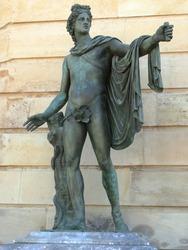 Green bronze sculpture symbolizing a man with a cape