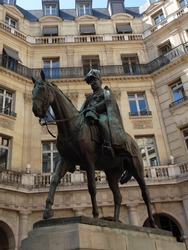 Green colored bronze sculpture symbolizing a man riding a horse