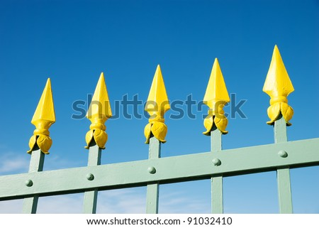 green fence with yellow arrows against blue sky