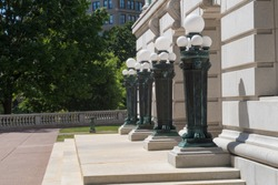 4 green lamp posts each with 5 globes