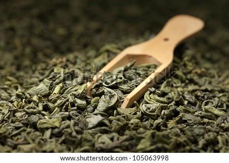 Green tea leaves full frame and wooden scoop