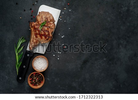Grilled beef steak on a knife with spices on a stone background with copy space for your text
