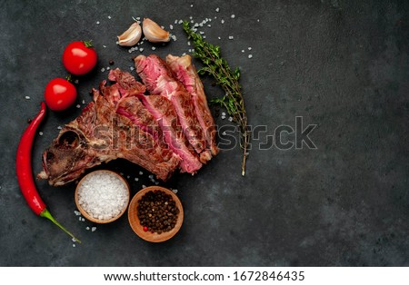 Grilled beef steak with spices on a stone background with copy space for your text.