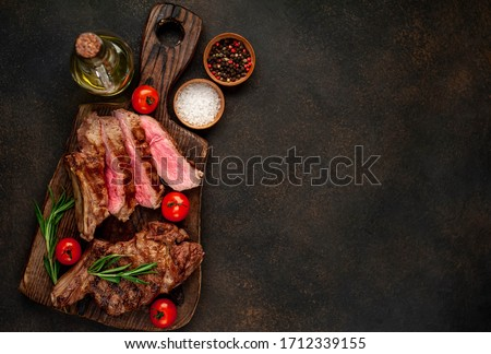 grilled beef steaks with spices on a cutting board on a stone background with copy space for your text