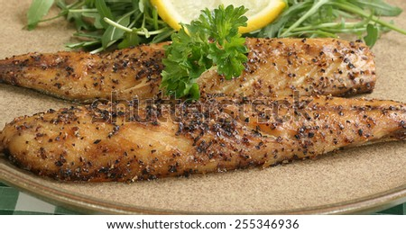 grilled mackerel fillets seasoned with pepper corns with lemon and parsley