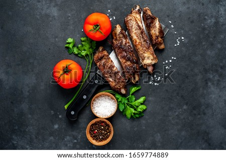 grilled pork ribs over meat knife with spices on a stone background
