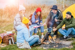 Group friends camping leisure and destination travel. Five people sitting around camp fire drinking hot tea, warming, joking together. Tourism relax and travel near lake in holiday. Sun glare